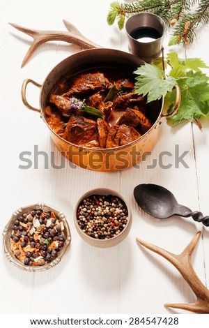 Delicious spicy venison goulash with diced deer meat in a copper pot with spice rub and red wine used in the marinade, high angle on white - stock photo