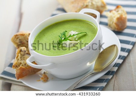 Delicious spinach cream soup with rye bread on a table. International meal. - stock photo