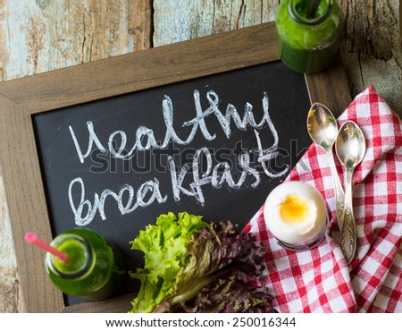Delicious spinach smoothie and boiled eggs on the wooden table - stock photo