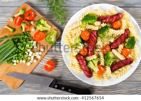 Delicious Spiral Pasta salad with broccoli and grilled sausages decorated with dill on a white dish, fresh chopped vegetables on cutting board, top view - stock photo