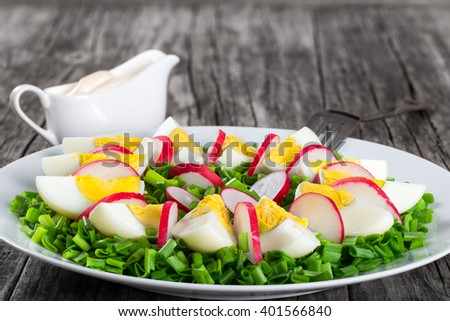 Delicious Spring onion, eggs, radish salad in a white dish with fork on an old rustic table, simply and easy recipe, horizontal close-up - stock photo