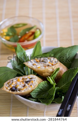 Delicious spring roll appetizer broken open to display the filling served with a fresh herb salad close up high angle view - stock photo