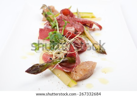 delicious starter, raw marinated green asparagus, chopped smoked duck breast and banana chutney,  - stock photo