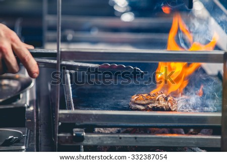 Delicious steak on the grill with fire and metal tongs in human hand close up - stock photo