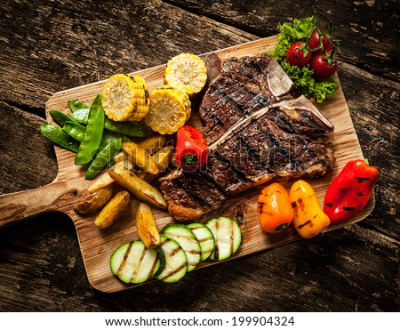 Delicious steakhouse porterhouse steak and colorful fresh roast vegetables with mangetout peas, corn, zucchini, bell pepper, potato and tomato on a wooden board, view from above - stock photo