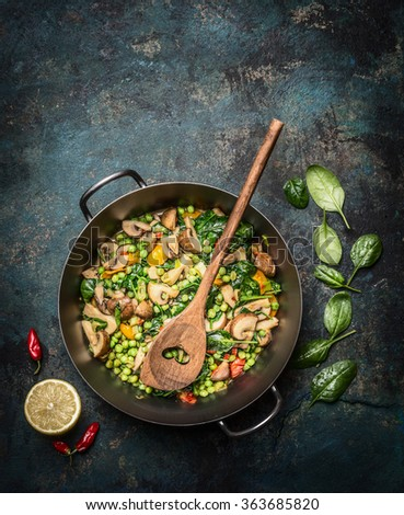 Delicious steamed healthy vegetables in cooking pan with ingredients and wooden spoon on dark rustic background, top view.  Vegetarian food or diet nutrition concept. Vertical. - stock photo