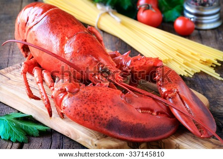 Delicious steamed lobster on wooden cutting board and spaghetti at the background - stock photo