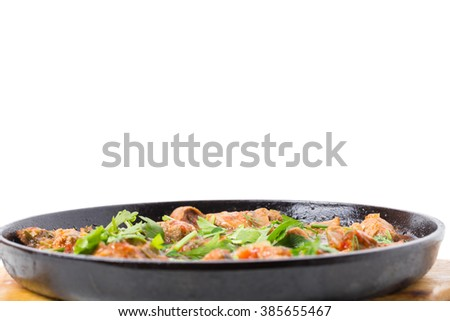 Delicious stewed lamb fillet with tomatoes and fresh parsley in cast iron pan. Isolated on a white background.