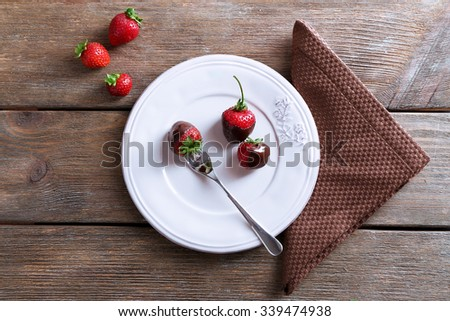 Delicious strawberries in chocolate and a brown napkin on wooden background - stock photo