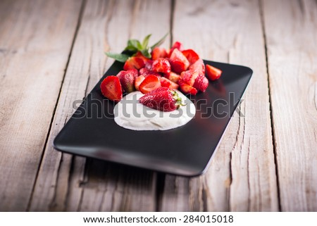 Delicious strawberries with sour cream on a plate; fresh ingredients for a smoothie - stock photo