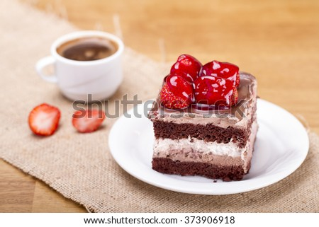delicious strawberry and chocolate cake on a wood table - stock photo
