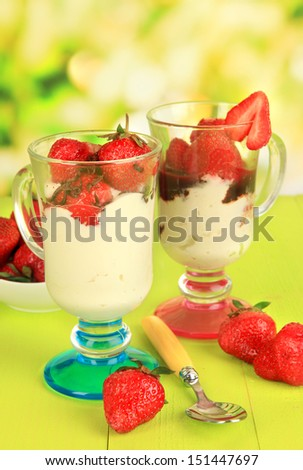 Delicious strawberry desserts in glass vase on wooden table on natural background
