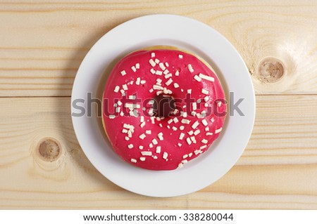 Delicious strawberry donut in plate on wooden background, top view  - stock photo