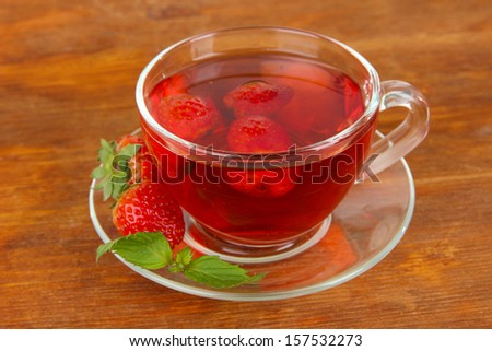 Delicious strawberry tea on table close-up