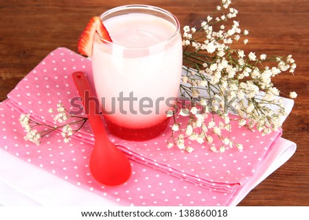 Delicious strawberry yogurt in glass on wooden table close-up