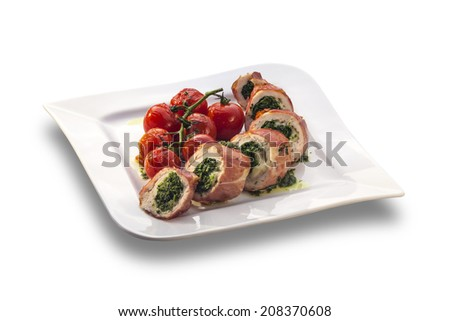Delicious stuffed chicken roll decorated with roasted cherry tomatoes isolated on white plate - stock photo
