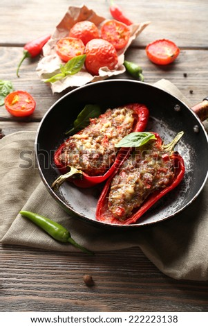 Delicious stuffed peppers in frying pan on table close-up - stock photo