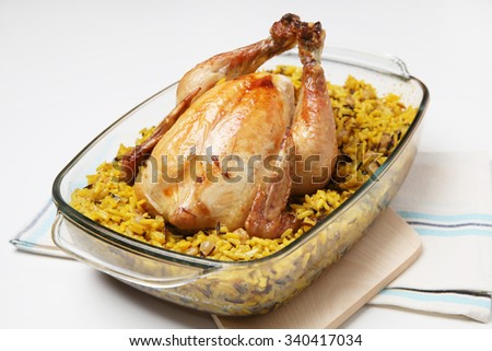 Delicious stuffed roast chicken in a baking tray with curry rice - stock photo