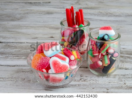 Delicious sugar sweets in glass bowl and jars - stock photo