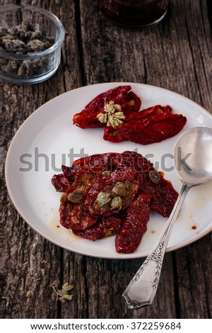 Delicious Sun Dried Tomatoes with Oregano and Capers. Traditional Italian food vegetables. - stock photo
