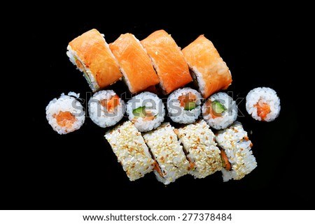 Delicious sushi rolls  on black background - stock photo