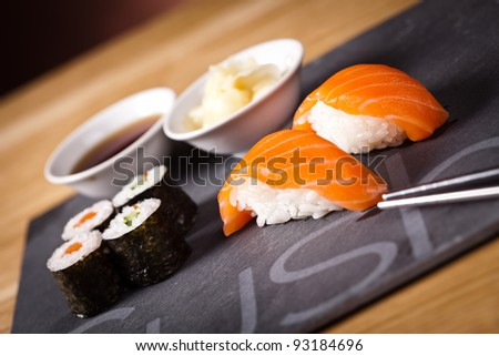 Delicious sushi rolls on white plate with chopsticks