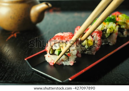 Delicious sushi rolls served on black wood plate with chopsticks - stock photo