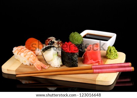 delicious sushi served on wooden board isolated on black - stock photo