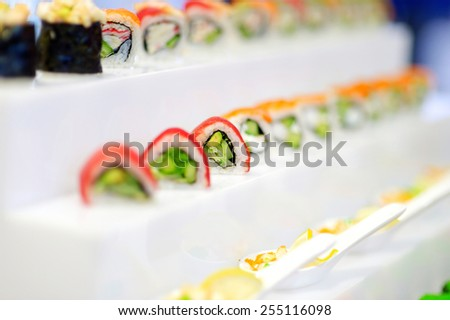 Delicious sushi with avocado topping on rolled seafood and rice arranged in a row on a tray at a catered event - stock photo