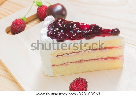 delicious sweet blueberry cheese cake on wooden with strawberry fruit on wood background can use in magazine book or brochure or introduce about ingredient