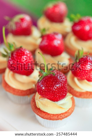 Delicious sweet buffet with cupcakes topped with berry - stock photo