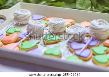 Delicious sweet buffet with heart-shaped cookies and marshmallow on sticks - stock photo