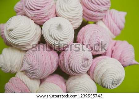 Delicious sweet buffet with homemade pink and white zephyr. Russian marshmallows. On a green background, selective focus