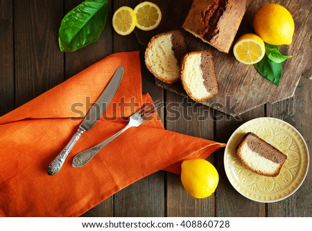 Delicious sweet cake bread with lemons on wooden table, top view - stock photo