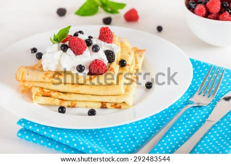 Delicious sweet crepes decorated air-cream and ripe berries, raspberries, blackberries and blueberries on a white plate, fork, knife, bright blue polka dot napkin. Tasty breakfast. - stock photo