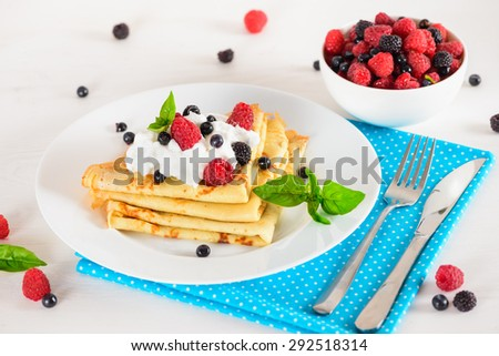 Delicious sweet crepes decorated air cream and ripe berries, raspberries, blackberries and blueberries on a white plate, fork, knife, bright blue polka dot napkin. Tasty breakfast . - stock photo