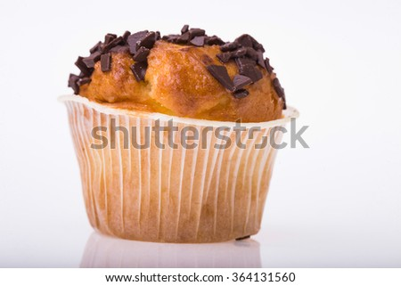 Delicious sweet dessert cupcake in paper basket with chocolate chips fattening food tasty baked refreshment isolated on white background closeup, horizontal picture - stock photo