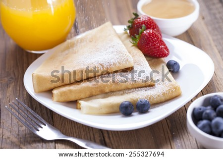 Delicious sweet French pancakes on a plate with fresh fruits and addons. - stock photo