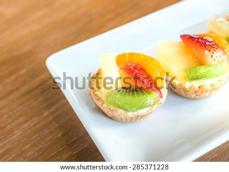 Delicious sweet fruit cake on white dish - stock photo