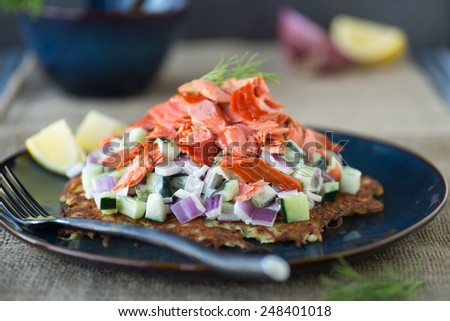 Delicious sweet potato rosti with cucumber salad and smoked salmon - stock photo