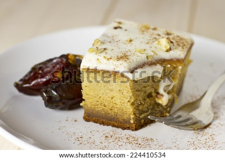 Delicious sweet pumpkin squash dessert cake  with dates on wood table. - stock photo