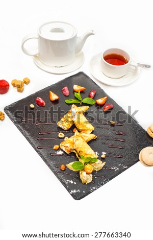 Delicious sweet rolled pancakes on a plate with fresh fruits - stock photo