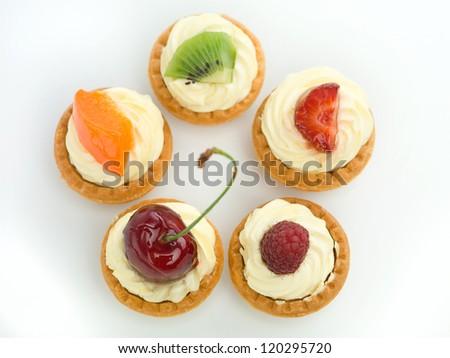 delicious tart arranged in circle with raspberry cherries kiwi strawberry apricot white background izolated - stock photo