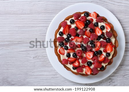 Delicious tart with fresh strawberries, raspberries and currants on the table. top view horizontal  - stock photo