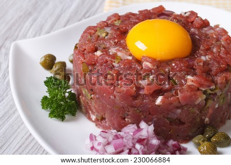 delicious tartare with egg yolk, onions and capers closeup on a white plate. horizontal  - stock photo