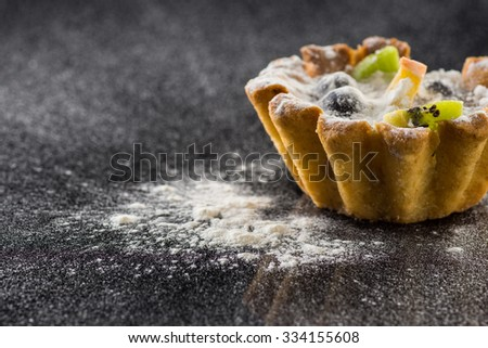 Delicious tartlet with fruit on black background - stock photo