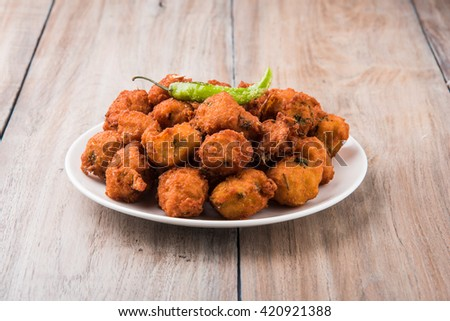 Delicious Tasty and Yummy Indian Moong Dal vada or moong dal pakoda or moong vade or Pakora (Fritter) with fried green chilli, red and green hot sauce.