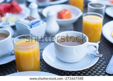 Delicious tasty cappuccino and fresh juice for breakfast at outdoor cafe - stock photo