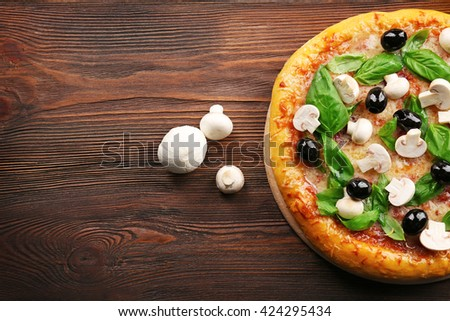 Delicious tasty pizza with ingredients on wooden table - stock photo