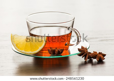 Delicious tea on the table next to lemon. - stock photo